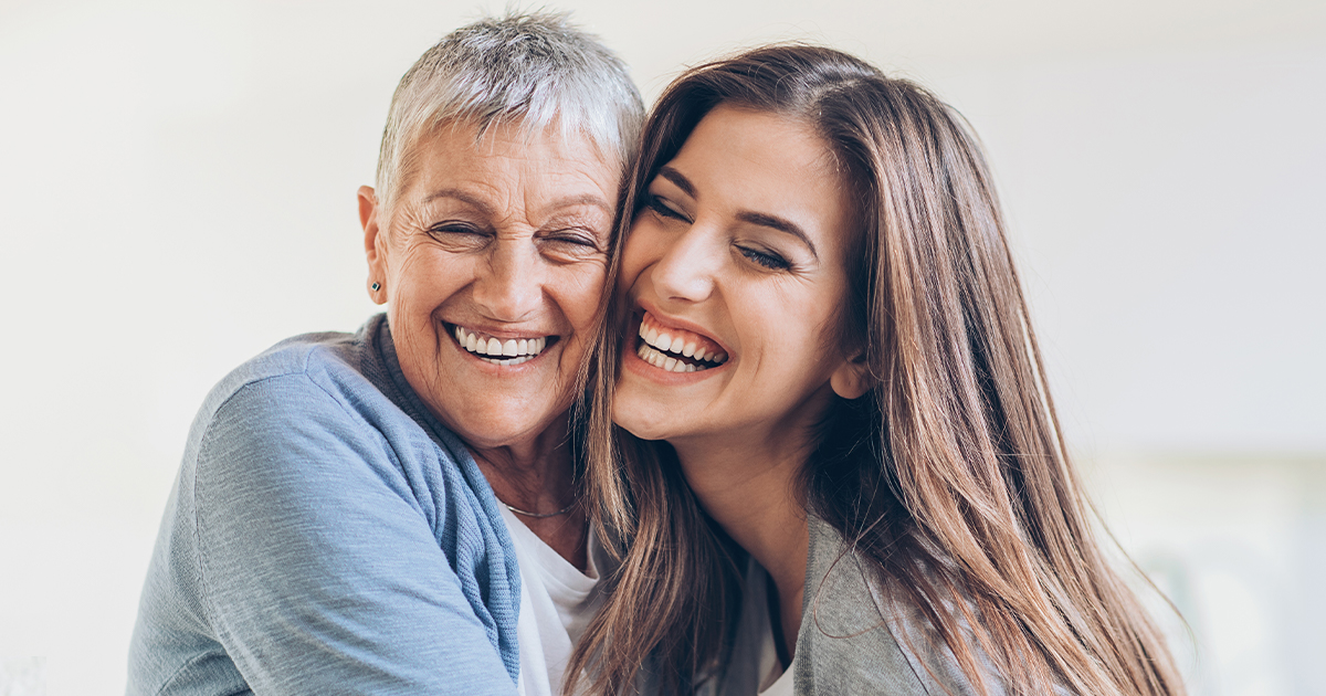 an older and younger woman hugging and laughing together - bladder health - Axia Women's Health