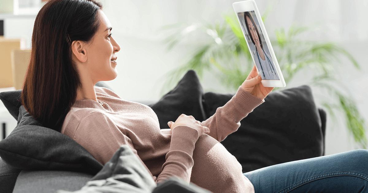 Pregnant woman using AxiaConnect Telemedicine form sofa - Axia Women's Health