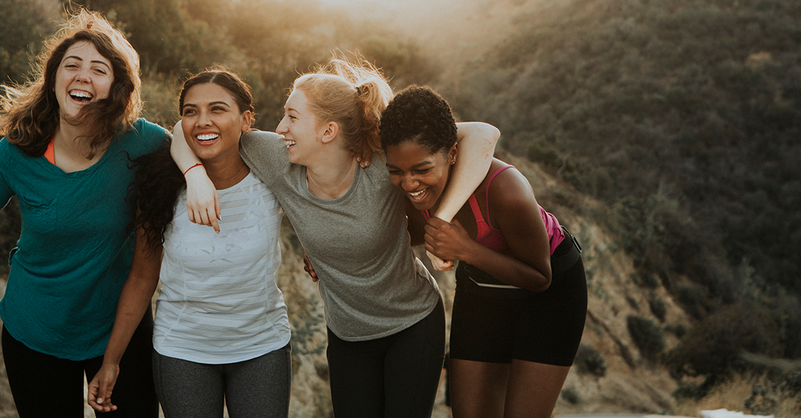 Women walking together outside hugging and laughing - Axia Women's Health - Women Deserve More