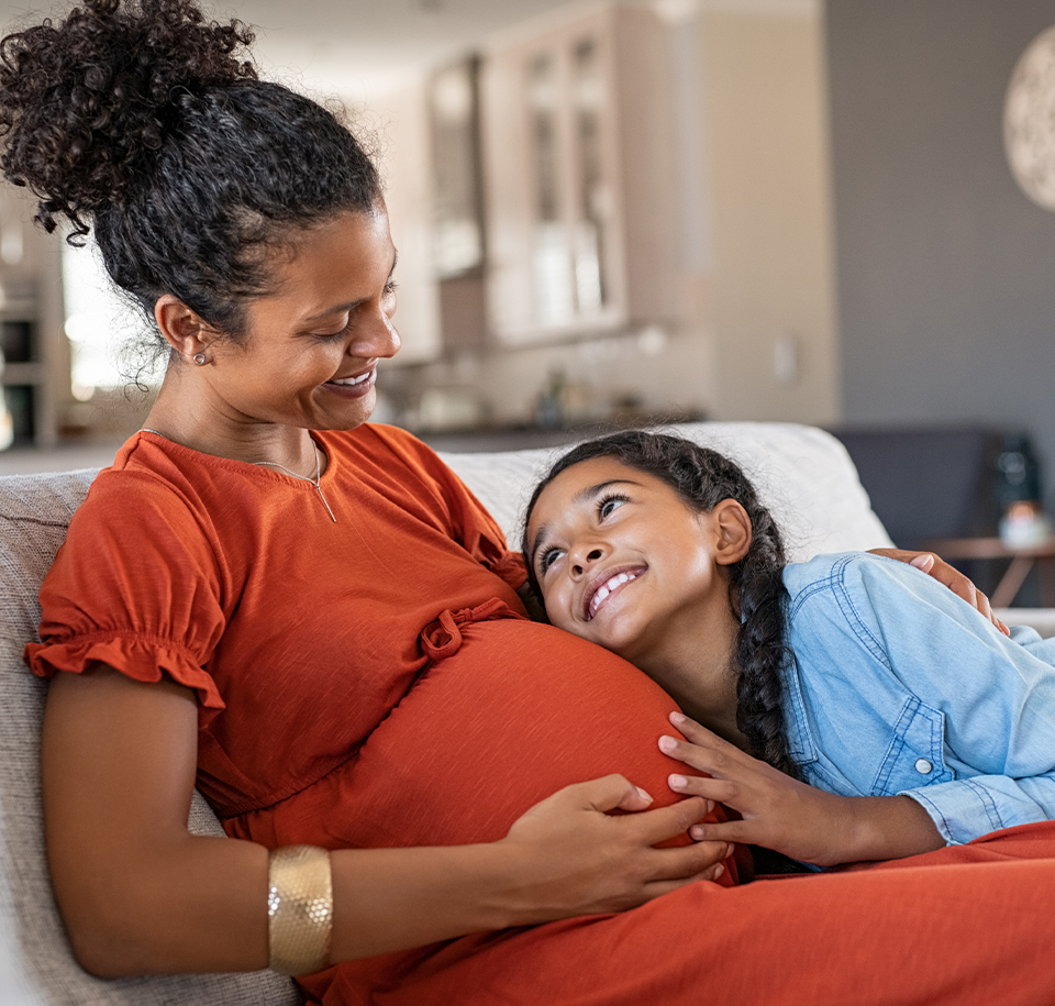 pregnant woman on couch with daughter - more personal care - Axia Women's Health