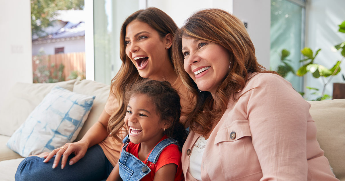 a mother, daughter, and granddaughter laughing together - Axia Women's Health